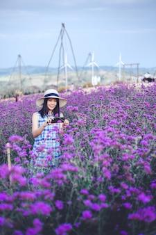 Podróży kobieta z purpurowym kwiatem