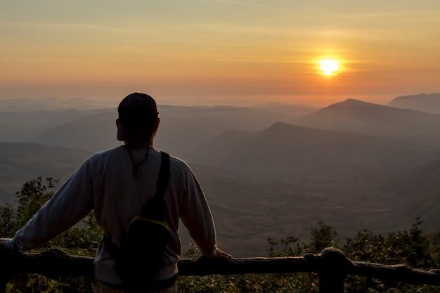 Podróży mężczyzn widok górski na wschód słońca.