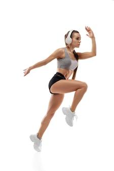 Podskoczyć. kaukaski profesjonalny lekkoatletka, trening biegacz na białym tle studio. umięśniona, wysportowana kobieta. koncepcja działania, ruchu, młodzieży, zdrowego stylu życia. miejsce na reklamę.