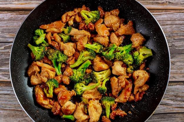Podsmaż na woku z kurczakiem i brokułami. chińskie jedzenie. ścieśniać.