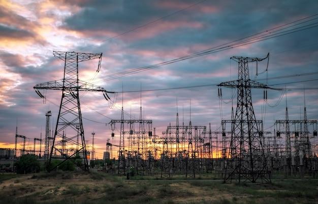 Podstacja elektryczna z liniami energetycznymi i transformatorami, o zachodzie słońca
