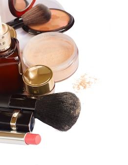 Podstawowe produkty do makijażu - podkład, puder i szminka na białym tle