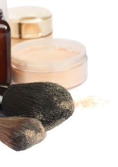 Podstawowe produkty do makijażu z miękkimi pędzlami na białym tle