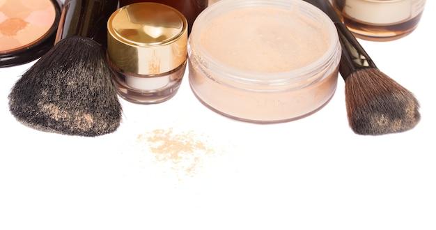 Podstawowe produkty do makijażu z szczotkowanym na białym tle