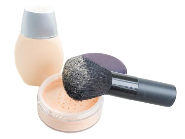 Podstawowy makijaż z pudrem, podkładem i pędzlem na białym tle