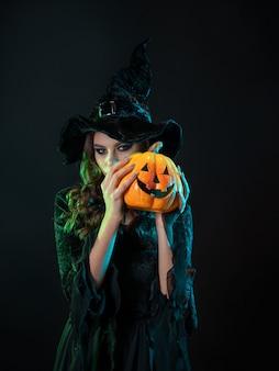 Podstępna piękna wiedźma w szpiczastym kapeluszu trzymająca dynię ze śmiejącą się twarzą