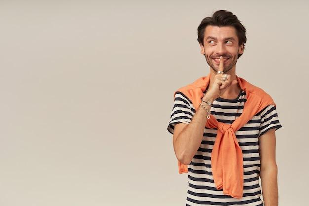 Podstępnie wyglądający facet z brunetką i włosiem. ubrana w t-shirt w paski i pomarańczowy sweter zawiązany na ramionach. pokazuje znak ciszy