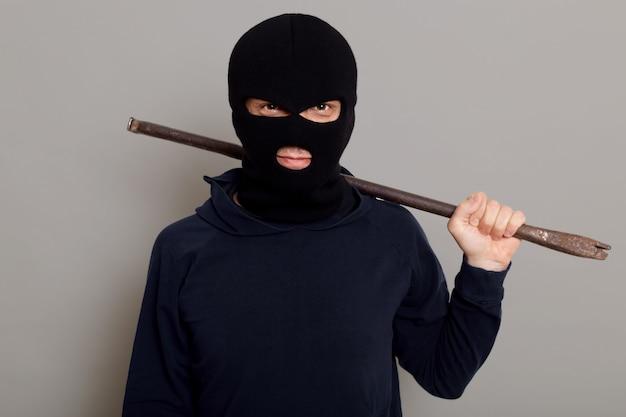 Podstępny męski złodziej złodziej patrzy na przód z uśmiechem