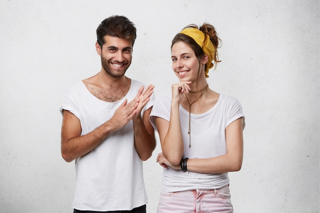 Podstępny, przebiegły i intrygujący młody europejczyk i kobieta ubrani w stylowe ubrania, wyglądający z tajemniczymi uśmiechami, mężczyzna wykonujący gest, jakby mył ręce