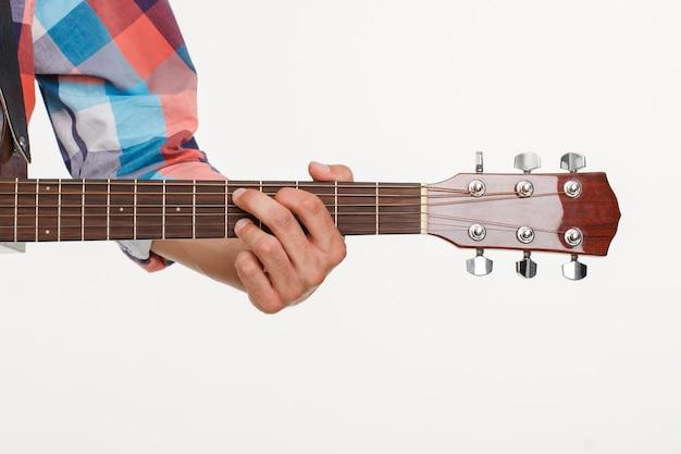 Podstrunnica gitary i ręka gra na gitarze. ręka mężczyzny trzymająca podstrunnicę. obraz podstrunnicy na białym tle.
