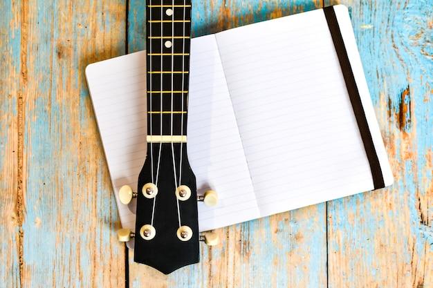 Podstrunnica ukulele i notatnik na drewnianym stole. niezależna nauka gry na hawajskiej gitarze online.