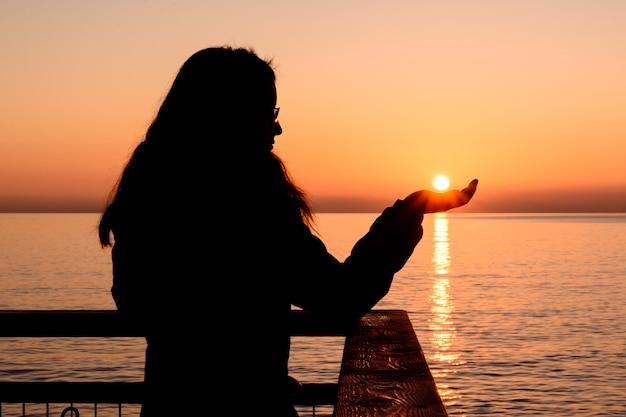Podświetlana dziewczyna podczas wschodu słońca łapie słońce rękami