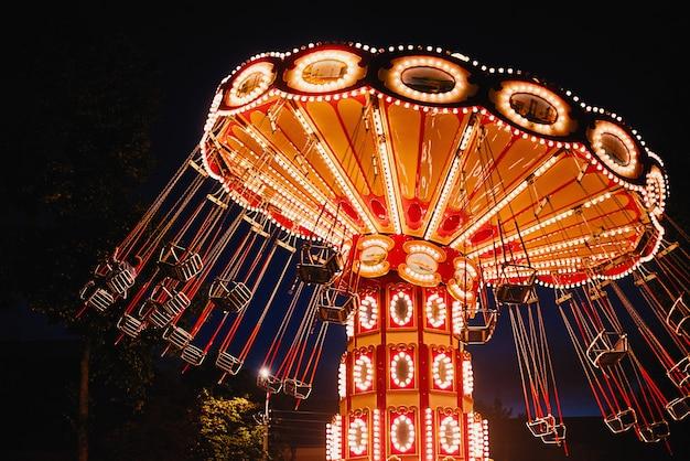 Podświetlana karuzela z huśtawką w parku rozrywki w nocy