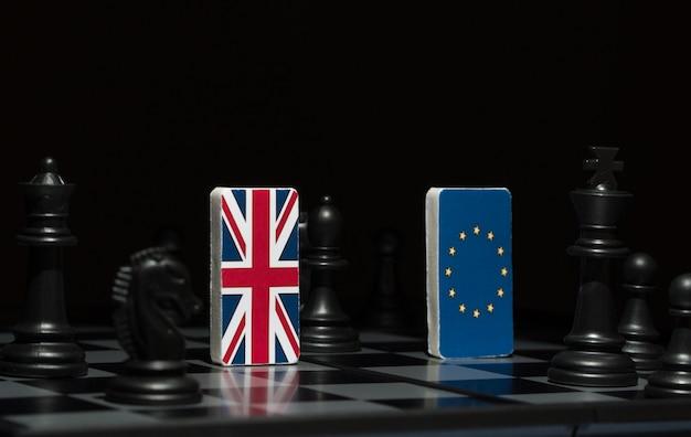 Podświetlane w cieniu postacie i flagi unii europejskiej i wielkiej brytanii na szachownicy