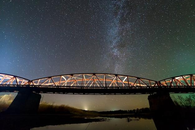 Podświetlany metalowy most na betonowych podporach odbity w wodzie na ciemnym gwiaździstym niebie na tle gwiazdozbioru drogi mlecznej. koncepcja fotografii nocnej.