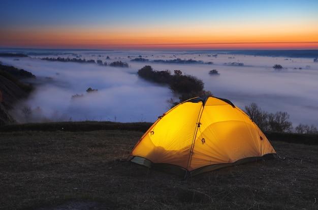 Podświetlany od wewnątrz pomarańczowy namiot turystyczny nad mglistą rzeką