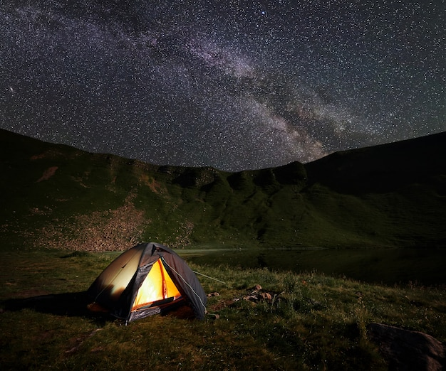 Podświetlany pomarańczowy namiot. nocne biwakowanie w górach w pobliżu jeziora pod niesamowitym pięknym niebem usianym gwiazdami i jasną drogą mleczną