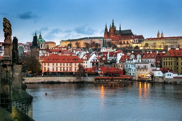 Podświetlany widok na mniejsze miasto od mostu karola wieczorem, z zamkiem praskim i kościołem świętego mikołaja w pradze, czechy