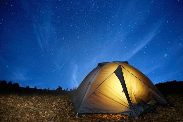 Podświetlany żółty namiot kempingowy pod gwiazdami w nocy