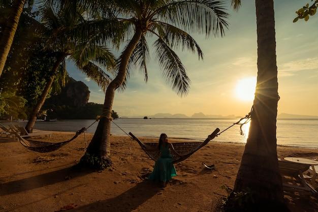 Podświetlenie sylwetka rano słońce plaża, drzewo kokosowe i kobieta na hamaku w koh yao noi, tajlandia