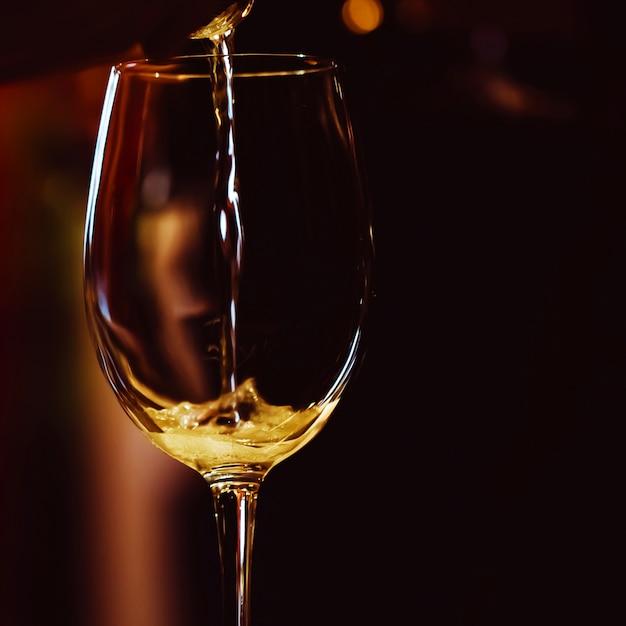 Podświetlona kieliszek do wina stoi na stole i wlewa się do niego strużka różowego szampana
