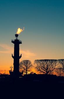 Podświetlona kolumna rostralna o zachodzie słońca. petersburg, wyspa wasiliewskiego.