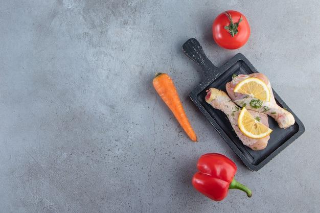 Podudzia i plasterki cytryny na desce obok warzyw, na marmurowym tle.