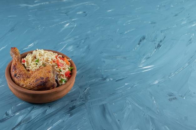 Podudzia z kurczaka i makaron w misce, na marmurowym tle.