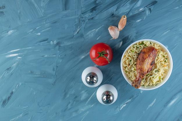 Podudzia z kurczaka i makaron w misce obok soli, pomidorów i czosnku, na marmurowym tle.