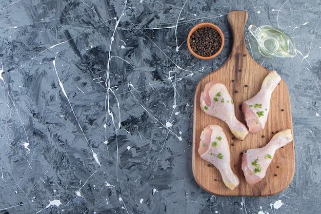 Podudzia z kurczaka na desce do krojenia obok misek na olej i przyprawy, na niebieskim tle.