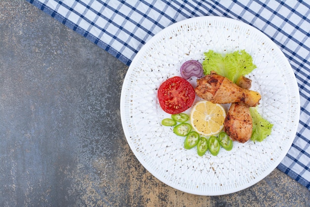 Podudzia z kurczaka z grilla na białym talerzu z warzywami. zdjęcie wysokiej jakości