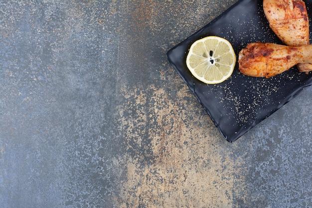 Podudzia z kurczaka z grilla na czarnej płycie z cytryną. zdjęcie wysokiej jakości