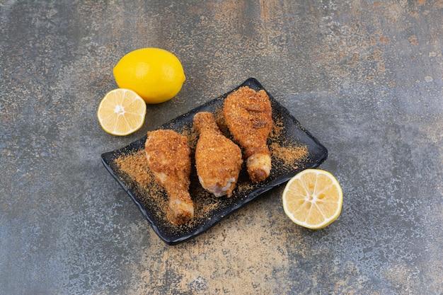 Podudzia z kurczaka z grilla na czarnej płycie z cytrynami. zdjęcie wysokiej jakości