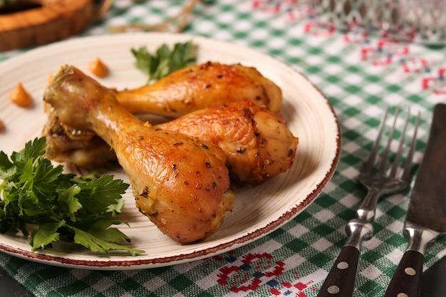 Podudzia z kurczaka zapiekane w marynacie musztardowej znajduje się na talerzu na ciemnym tle, zbliżenie