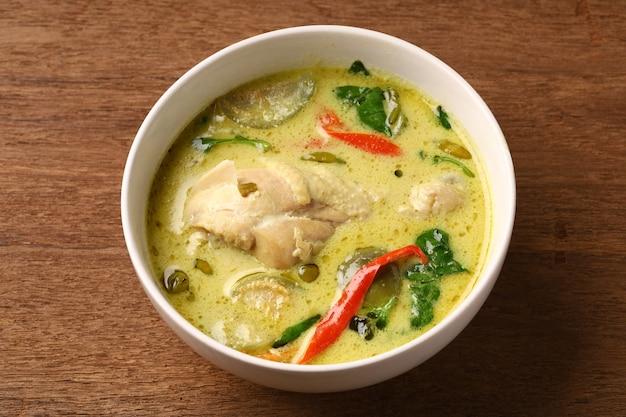 Podudzie z kurczaka zielone curry w okrągłej misce na starym drewnianym stole, tajska tradycyjna kuchnia