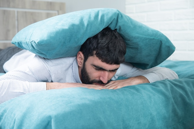 Poduszka smutny mężczyzna na głowie w łóżku