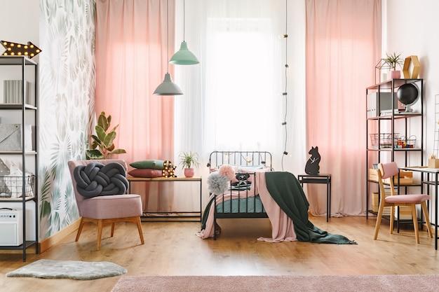 Poduszka węzeł na różowym fotelu w pastelowym wnętrzu sypialni dziewczynki z lampami i zasłonami