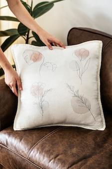 Poduszka z minimalistyczną grafiką w kwiaty na skórzanej kanapie