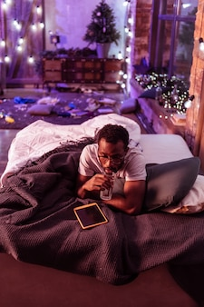 Poduszki i koce. zmęczony mężczyzna w przezroczystych okularach odpoczywa w łóżku, mając bałagan po imprezie po całej podłodze