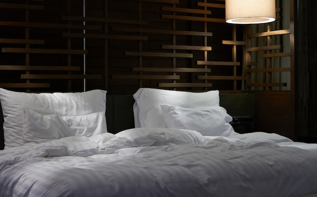 Poduszki i prześcieradło w pokoju hotelowym