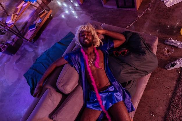 Poduszki i śmieci. afroamerykanin pijany mężczyzna śpi po szalonej nocy spędzonej z popcornem na całej podłodze