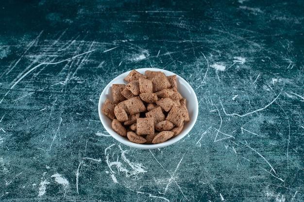 Poduszki kukurydziane w misce na niebieskiej powierzchni