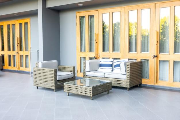 Poduszki z odkrytym tarasem patio i sofą na balkonie w ogrodzie