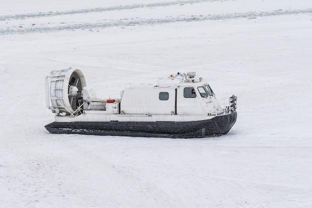 Poduszkowiec łódź na białym śniegu w zimie.