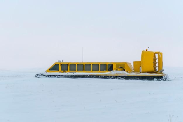 Poduszkowiec w zimowej tundrze. poduszka powietrzna na plaży. żółty poduszkowiec pod śniegiem.