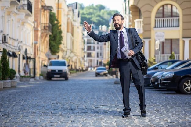 Podwieź mnie. pełnometrażowy pozytywny profesjonalny biznesmen stojący na ulicy, czekając na przejażdżkę