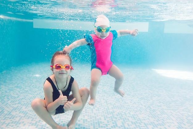 Podwodne młodzi przyjaciele w basenie