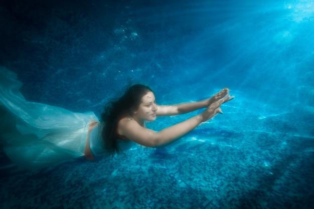 Podwodne ujęcie pięknej kobiety w sukience wyłania się z basenu w snopie światła