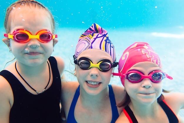 Podwodne zdjęcie młodych przyjaciół w basenie