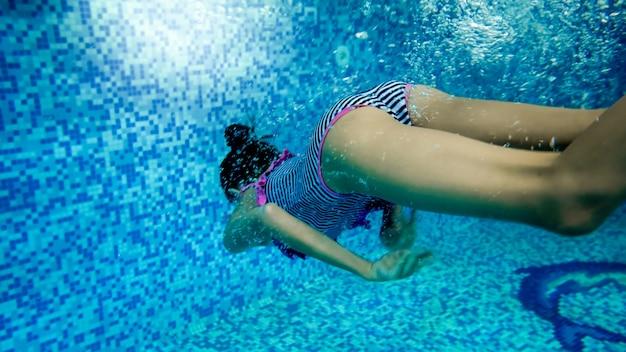 Podwodny obraz nastoletniej dziewczyny w pasiastym stroju kąpielowym, który nurkuje i pływa pod wodą na basenie
